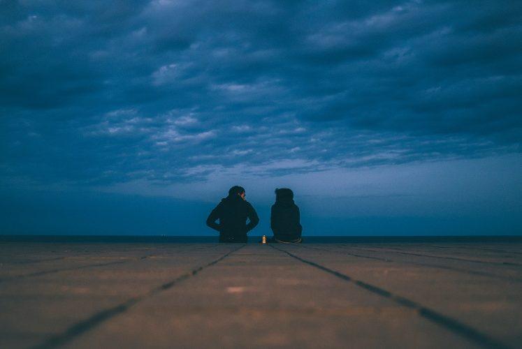 Zwei Personen im Gespräch auf dem Boden vor einem dunklen Himmel